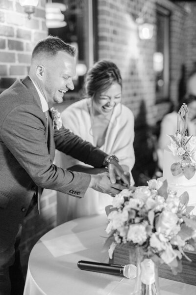 bride and groom smiling and cutting cake