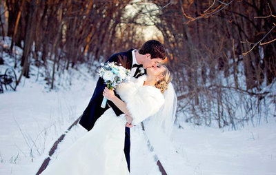 Groom kisses bride in the snow