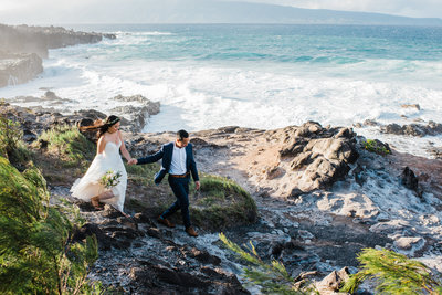 A groom leads his bride to a cliffside location in Maui, Hawaii