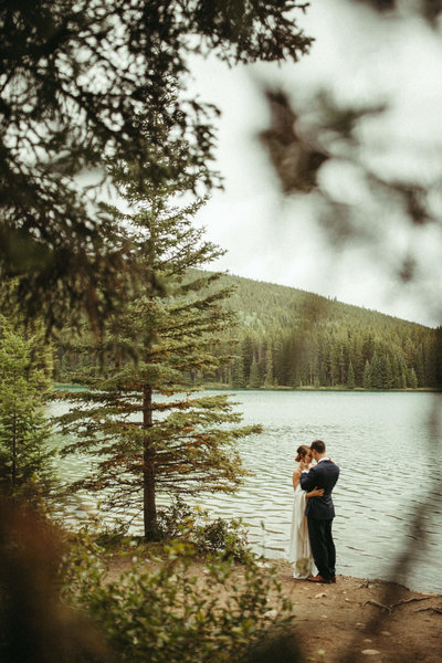bride and groom hugging while standing next to lake