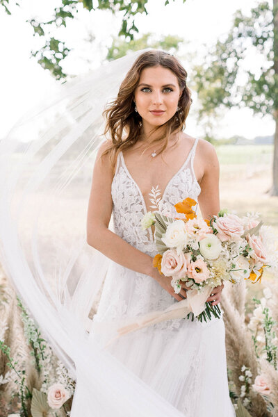 A beautiful bride holding a bouquet. Her wedding veil is swinging out around her and her dress is all lace