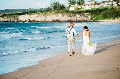 A bride and groom stroll along the sand in Kapalua Maui Hawaii