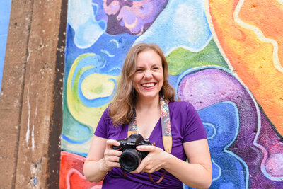 Photographer Kristen Hazelton holding a camera  in front of a colorful mural alongside the Green El line