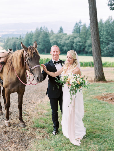 film portrait of a bride and groom with a horse