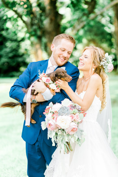 Bride and groom laugh while playing with puppy wearing a flower crown