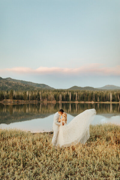 bride and groom kissing in a field with mountains behind them