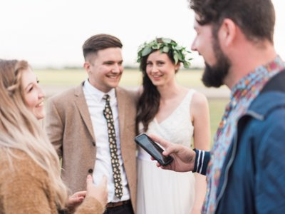 Man holds phone while talking with bride and groom