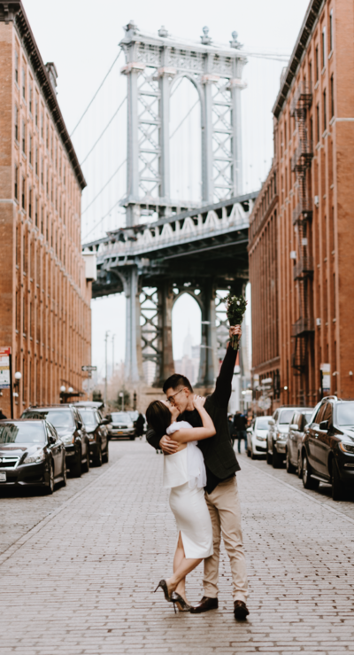 man holds up a bouquet triumphantly while he kisses his fiancee in dumbo brooklyn in nyc in front of the manhattan bridge