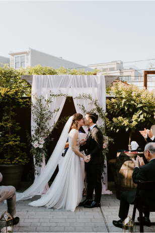 bride and groom share their first kiss during their wedding ceremony at the gallery o on h in washington dc