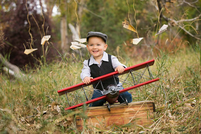 Toddler boy playing with a toy plane during a photo shoot
