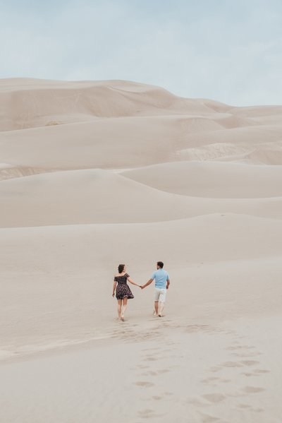 Couple walks holding hands across the landscape at Great Sand Dunes National Park in Colorado for their engagement photos