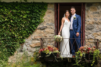 Bride and groom embrace and smile on Juliet balcony overlooking a garden