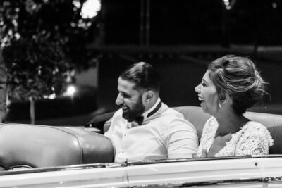 Bride and groom sitting together laughing in their vintage wedding car