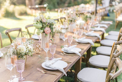 Table setting with pink water glasses and boho flowers at Gardener Ranch wedding