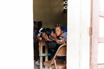 Haitian children looking out doorway