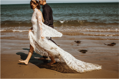 bride-and-groom-walking-on-beach@2x