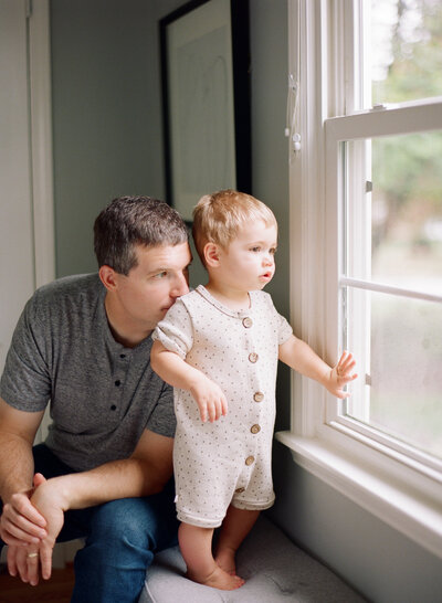 Father and toddler look out the window