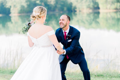 amazing first look reaction of groom seeing his bride for the first time by the lake at foxhall resort by atlanta wedding photographer lane albers photography