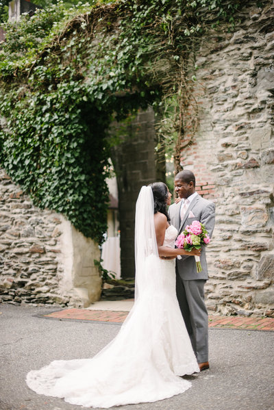 couple in front of a rusti over grown wall of ivy and vines for their old mill in philadelphia wedding