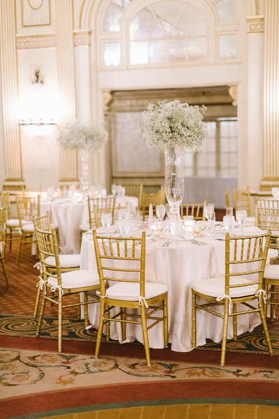 tall baby breath centerpieces in tall glass vases on the round tables at the brown hotel by roots floral design