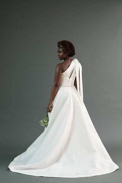 Back view of the Kimi wedding dress with its asymmetrical neckline and a-line skirt