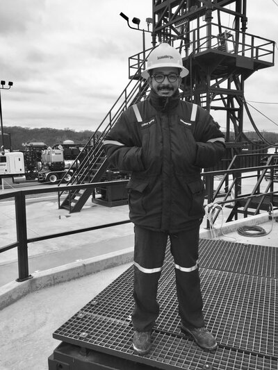 a man in a hard hat stands on an oil rig