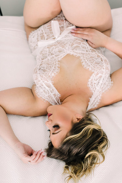 A woman wearing white lingerie poses for a bridal boudoir shoot in Chicago.