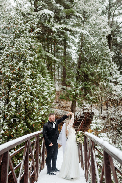 Groom twirls bride on a bridge in the woods covered in snow