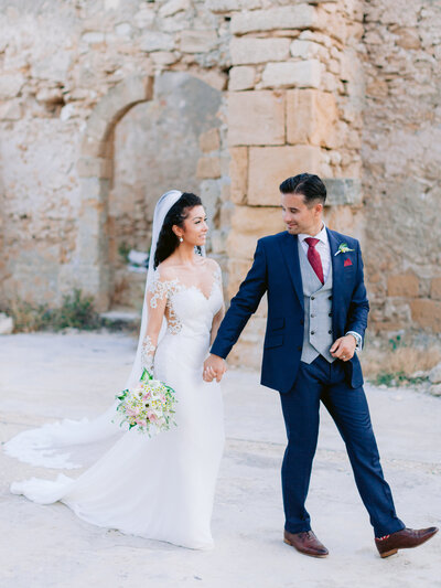 Bride and Groom walk hand in hand through the Sicilian ruins