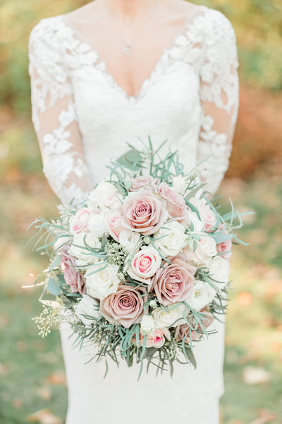 Close up detail shot of a bride holding her bouquet of pink and white roses.