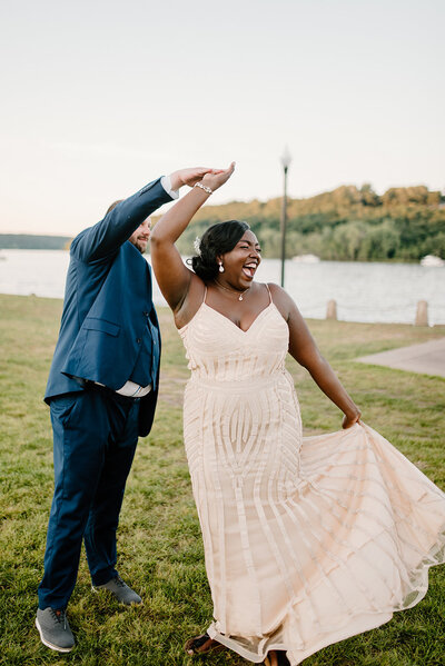 Groom twirls bride as she laughs with an open mouth