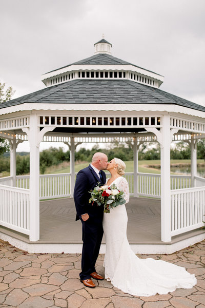 Bride & Groom kissing in front of white gazebo at Fire Stables