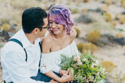 Adventurous couple cuddles up in the desert at their elopement