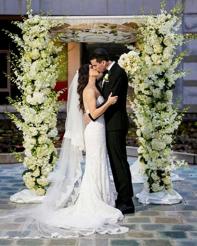 Rebecca and Ben kiss in front of their Chuppah following their Jewish wedding ceremony at Skirball Cultural Center in LA.