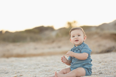Baby Boy Sits on the Beach with Sand Dunes in the Background During a Ponte Vedre Beach Family Photo Session