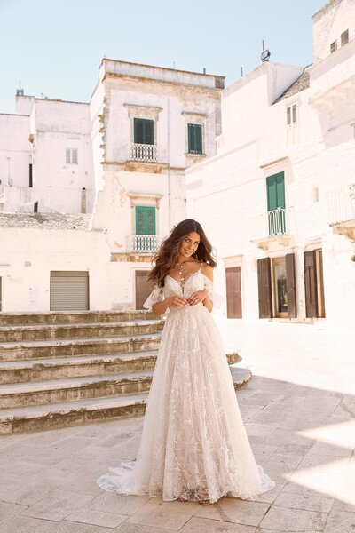 As the sunset seeps between the sails and the sea breeze blows, Maiya looks out over the bow, as she sets sail somewhere off the Italian coastline. She is the summer elegance that offers three very unique and very versatile looks, that makes Maiya a gown to reckon with. Her transparent large floral appliqués are found all over her A line design which seamlessly flows from the bodice to her billowing skirt. Her shoe string straps are simple, elegantly connecting to her low, sheer lace back. Maiya's V neckline is modest allowing brides to accessories how they please to add their own personal touch. What makes Maiya a stand-out gown is her understated ability to meet the needs of her future bride. A detachable sheer embroidered jacket can be slipped on and tied in a bow where the V neckline comes to stop creating a very sophisticated style. For more of a bohemian beach wedding, detachable lace off the shoulder appliqués are attached for a fun and flirty touch. Maiya also offers a custom Madi Lane veil which perfectly matches the floral lace motifs which add to her traditional cathedral length gown – the extra touch that softly trails behind making Maiya just magical.