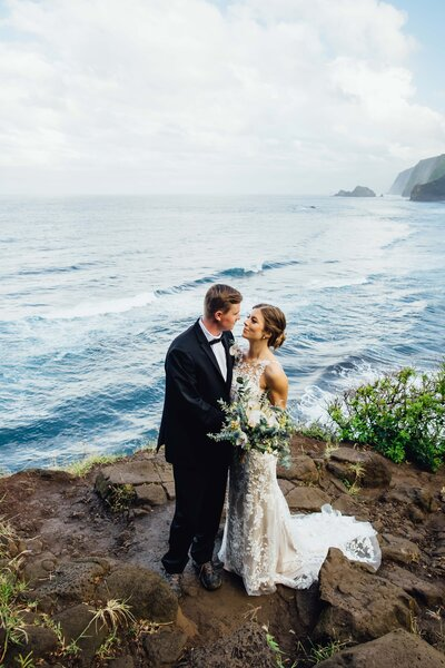 bride and groom on hawaii cliff