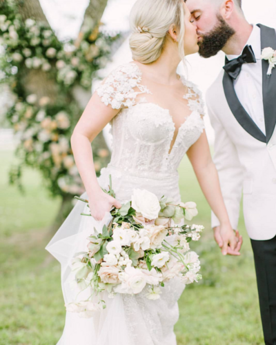 A fine art image of a bride and groom kissing. The bride is wearing a gorgeous lace gown with a white and pink bouquet. The groom has on a white and black tuxedo