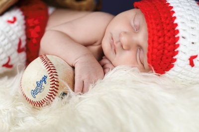 Beautiful Mississippi Newborn Photography: Baby boy wears baseball outfit and holds Rawlings baseball