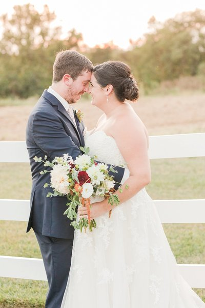 bride and groom hugging by fence at the belmont farm in southern maryland by costola photography