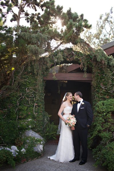 Bride and Groom in front of rock wall at the Lodge at Torrey Pines