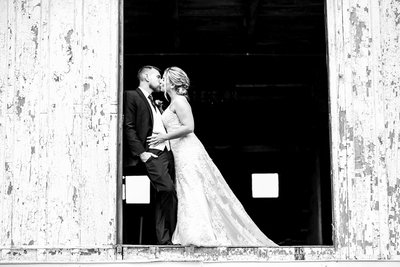 Bride and groom kiss on the second floor of the barn at The Barn at Conneaut Creek