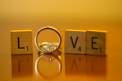 "Scrabble tiles with wedding rings spell ""Love"". Photo by Ross Photography, Trinidad, W.I.."