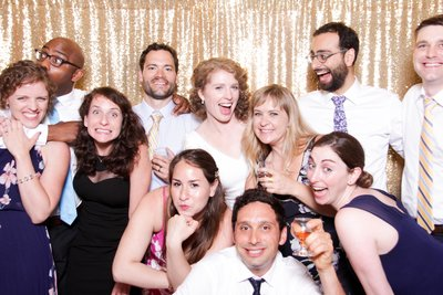 bride  and groom next to their families having a great time front of the photo booth.