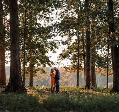 an engaged couple between the trees foreheads together