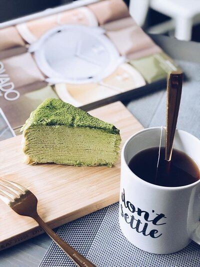 flat lay of nakeia homer white don't settle mug with a slice of green cake and a gold fork