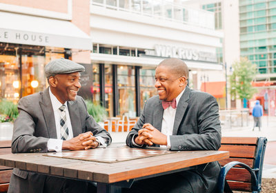 Two gentleman sitting outdoors on a wooden table with a chess mat staring at each other and smiling