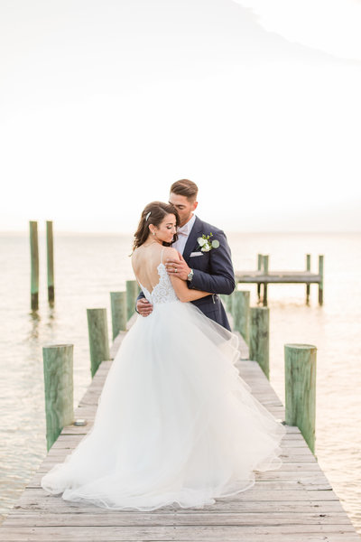couple standing on pier at weatherly farm and pavilion on wedding day by costola photography