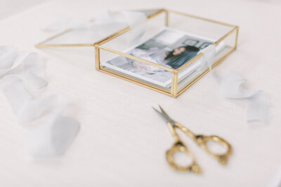 Newborn session prints in gold box with ribbon and vintage scissors nearby