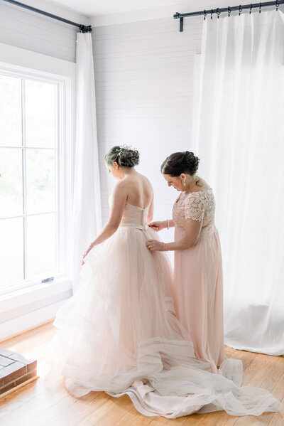 bride and mother getting dressed